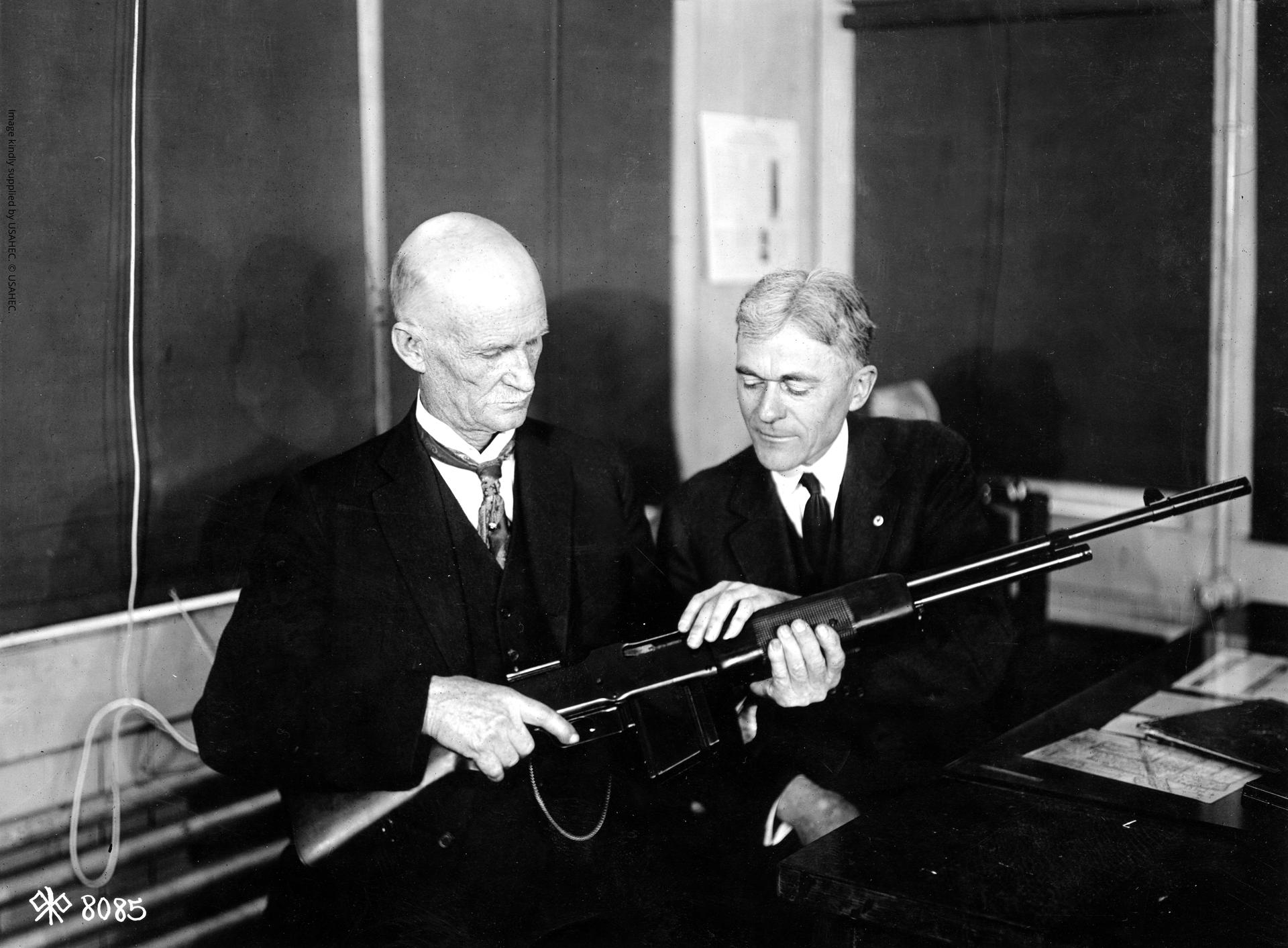 Photograph showing inventor John Browning and Mr. Burton, the Winchester expert on rifles, discussing the fine points of the Browning Light Gun at the Winchester Plant (WWI Signal Corps Photograph Collection (RG4) Box 214).
