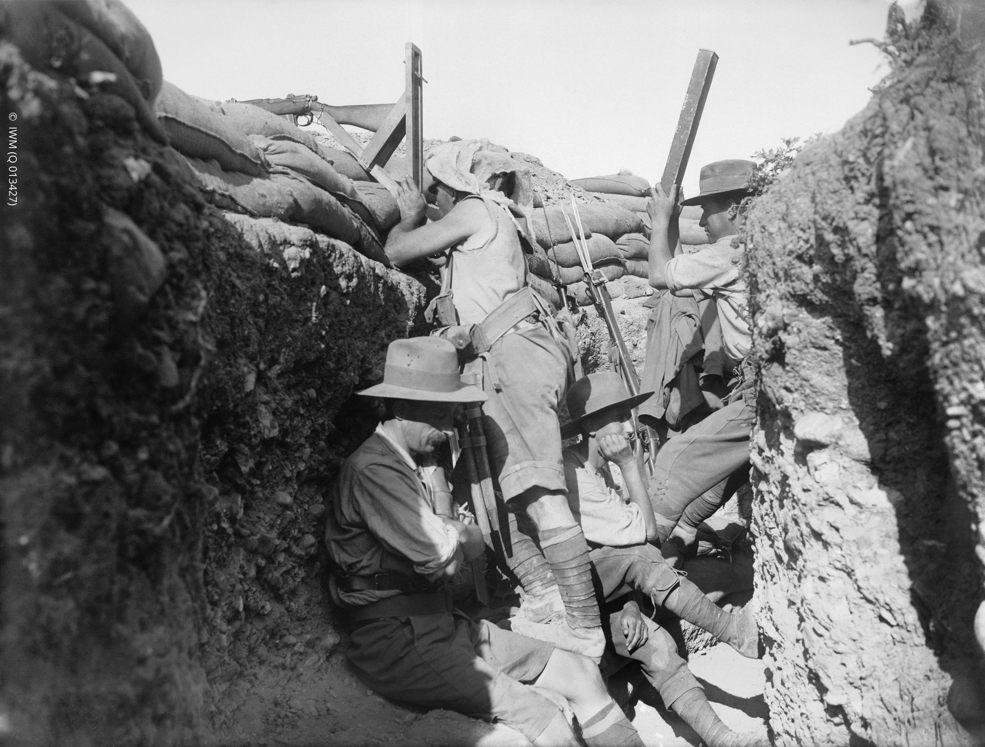 "Men of the Royal Naval Division and Australians in the same trench. One is using a ""sniperscope"" and another a periscope. Defence of the ANZAC. Scene in a trench during the period 28th April - 12th May, when the Marine and 1st Naval Brigades of the Royal Naval Division reinforced the Australian and New Zealand Army Corps in the area about what were later known as Quinn's and Courtney's Posts. The Marines brought a few periscopes with them, and the Australians improvised a supply from looking-glasses sent ashore from transports."