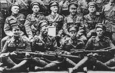 Thumbnail image of Canadian snipers of the 20th Battalion, CEF. The man front left holds an SMLE with Winchester A5 scope, the others appear to have SMLEs with PPCo scopes and mounts. The latter was offset, forcing the sniper to either raise their head from the stock when aiming, or to shoot with the left eye, compromising accuracy. Canada pursued the Ross rifle mainly because Britain would not provide them with SMLEs until later in the War. © Courtesy of Martin Pegler, private collection