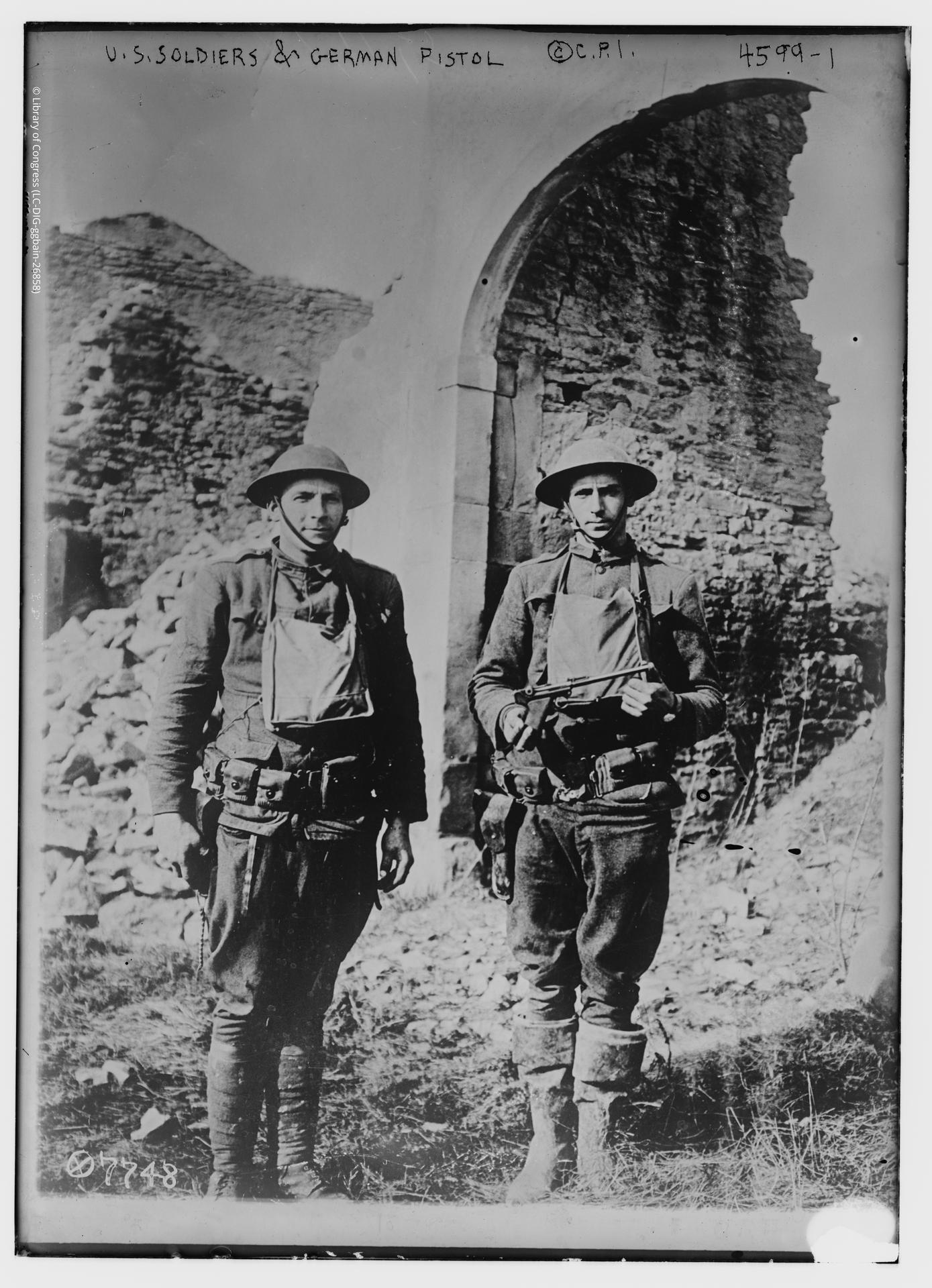 Photograph of US Soldiers and a German pistol.