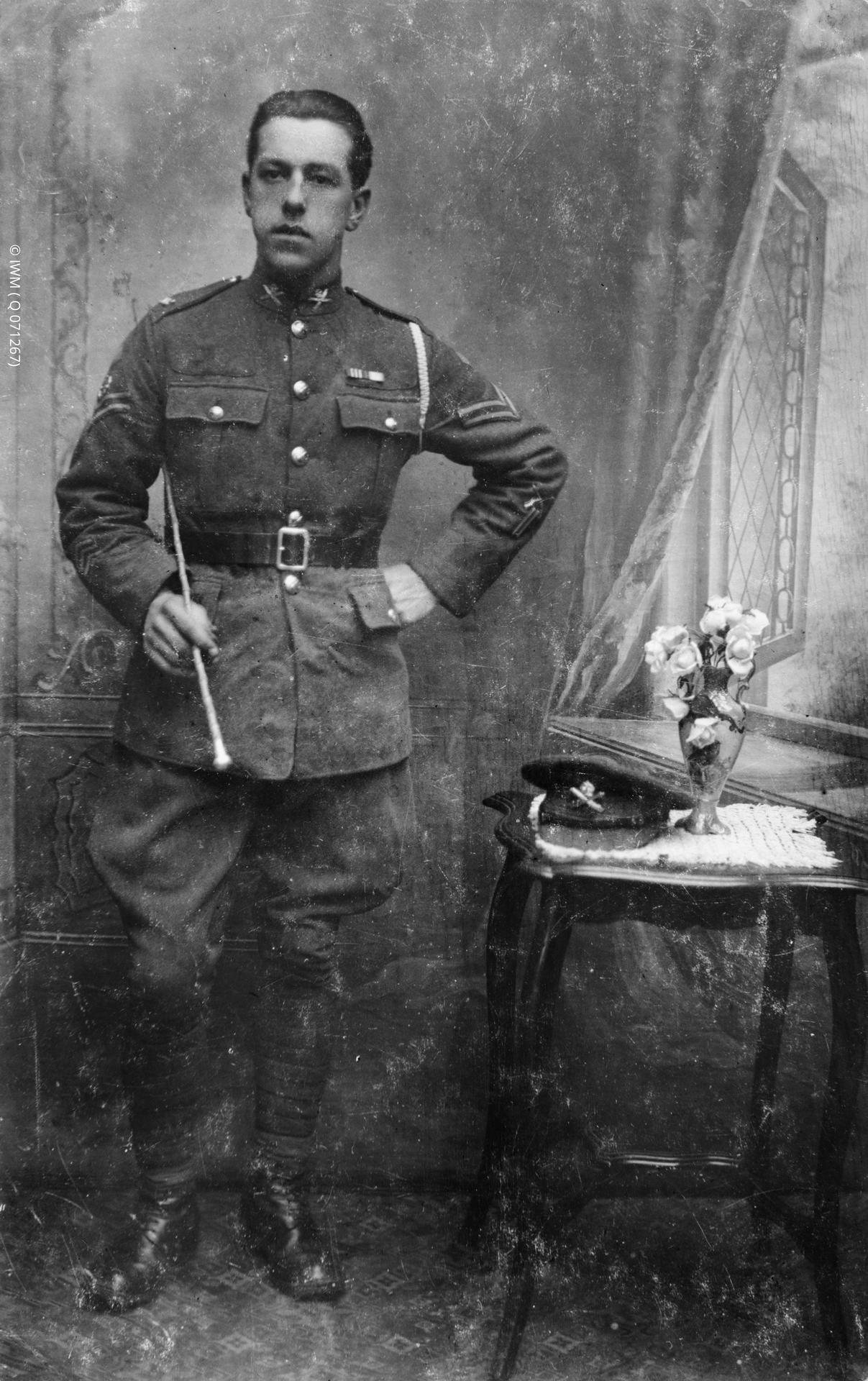 Copy negative created from a photograph. Image shows a formal, full-length studio portrait of Corporal George A Coppard MM standing. The photograph was presumable taken after the awarding of the Military Medal for services in the Battle of Cambrai.  Portrait photograph (formal). Coppard is seated wearing the uniform of a corporal in the Machine Gun Corps, with the ribbon to the MM on his tunic. Standing behind and to the side is another soldier, a sergeant.