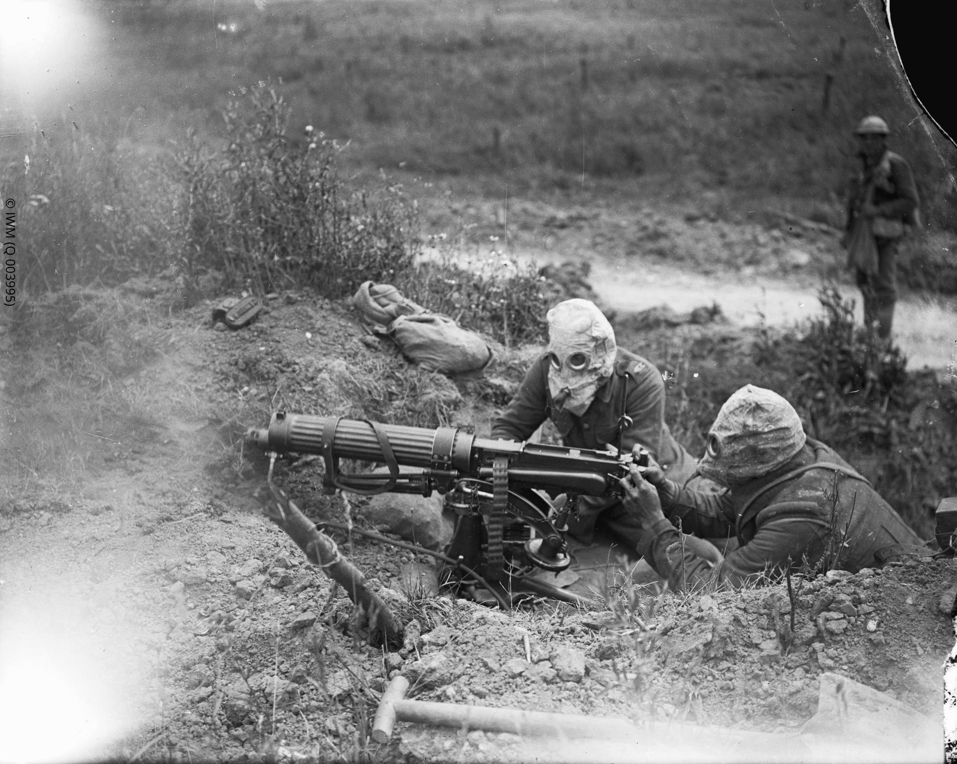 A Machine Gun Corps gun crew firing into a German communication trench near Ovillers, July 1916. The gun's sights are set beyond visual range, at around 2000 yards.