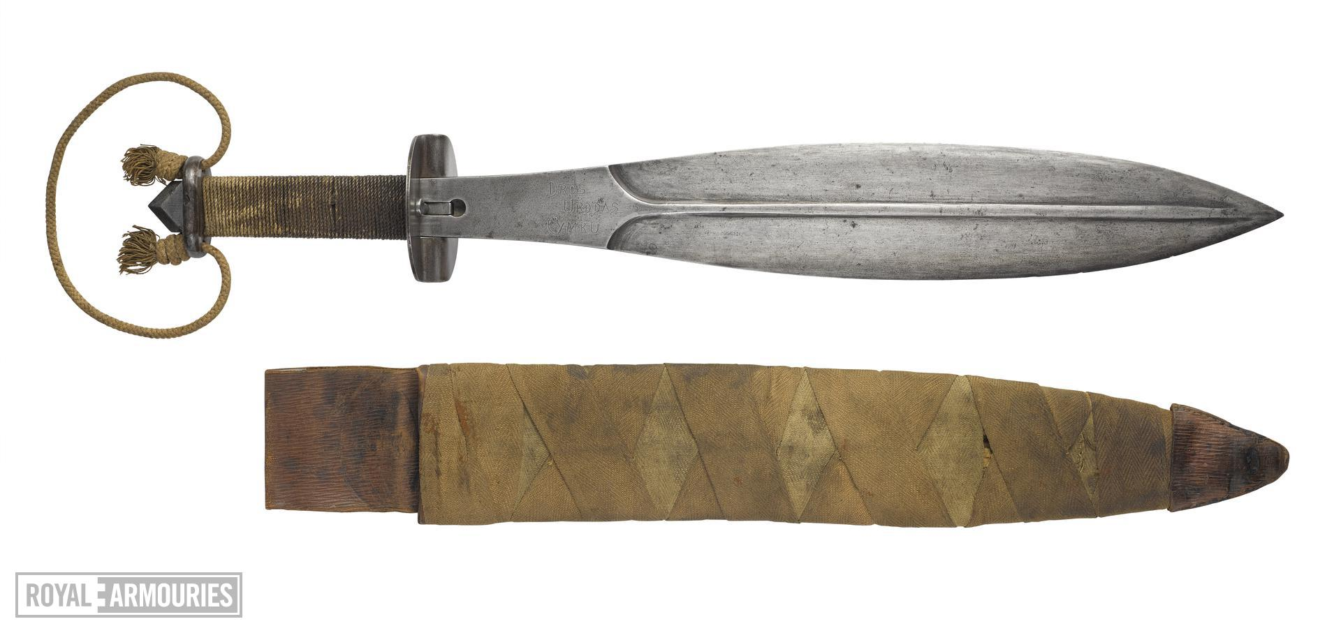 Short sword and scabbard (Trench knife), British, about 1917-1981. Used as a side arm by the 9th Service Battalion of the Royal Welsh Fusiliers.