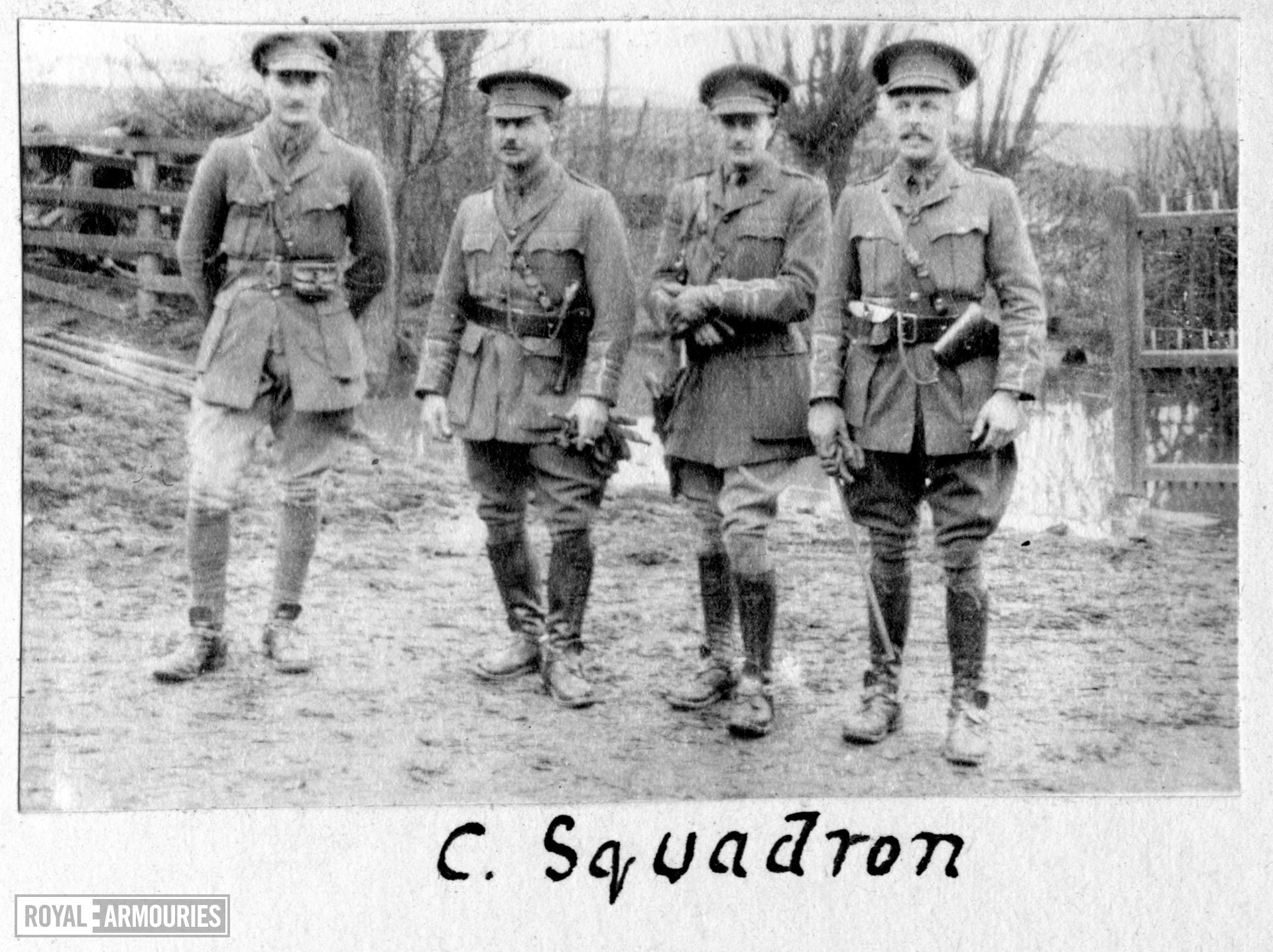Photograph of 4 officers of the 2nd Dragoon Guards armed with Webley revolvers, Western Front, 1914-1915, taken from a photograph album compiled by Captain F.D.R. Milne,  2nd Dragoon Guards (Queen's Bays) recording his service with the regiment from 1913 to 1918, and including some family photographs from the 1920s.