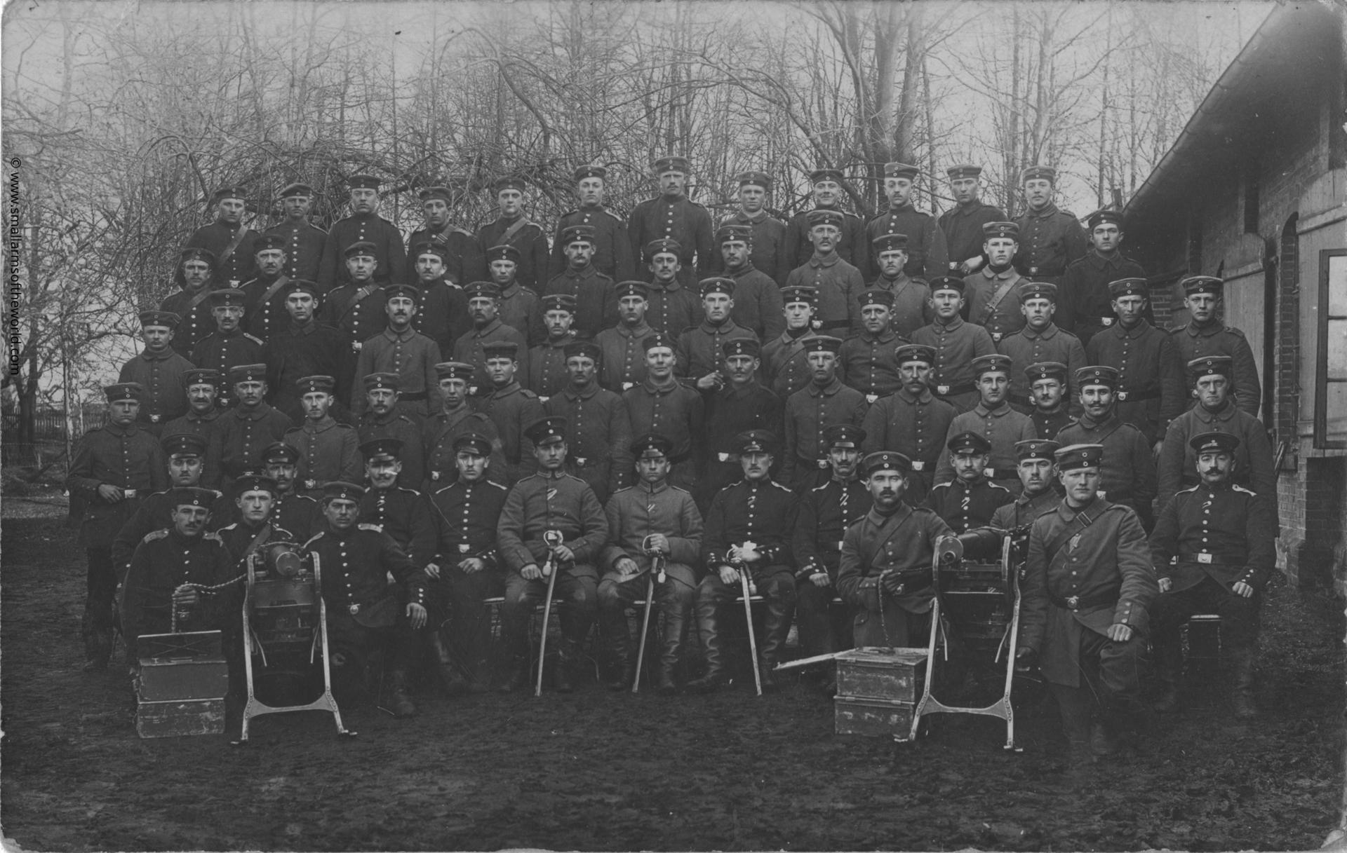 German soldiers that have been taking a machine gun training course. Note there are seven officers in the group, signified by their peaked caps. The gun is a Maxim MG08 on sled.