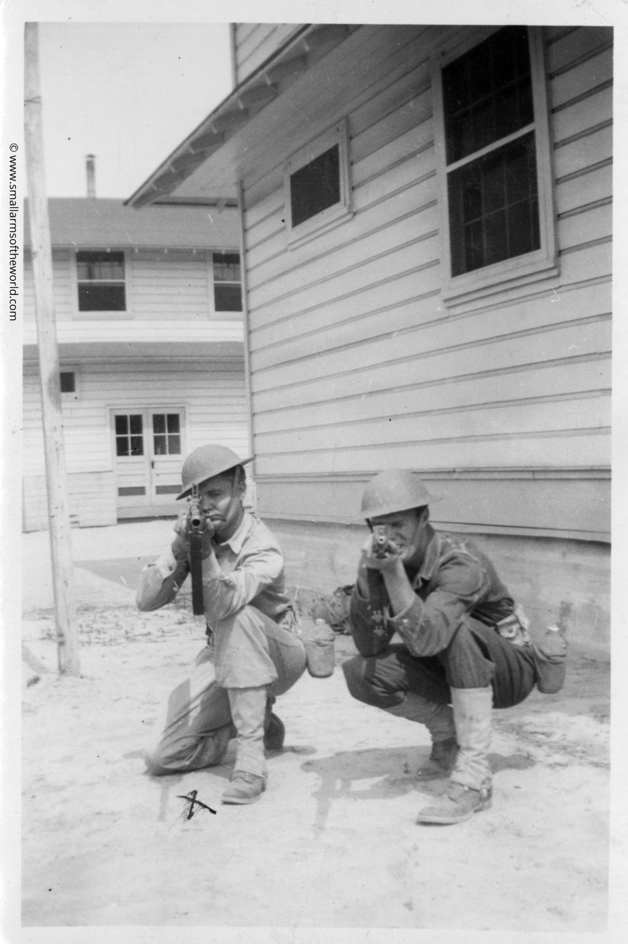 Two US soldiers with M1903 Springfield rifles next to a1930s style barracks.© www.smallarmsoftheworld.com