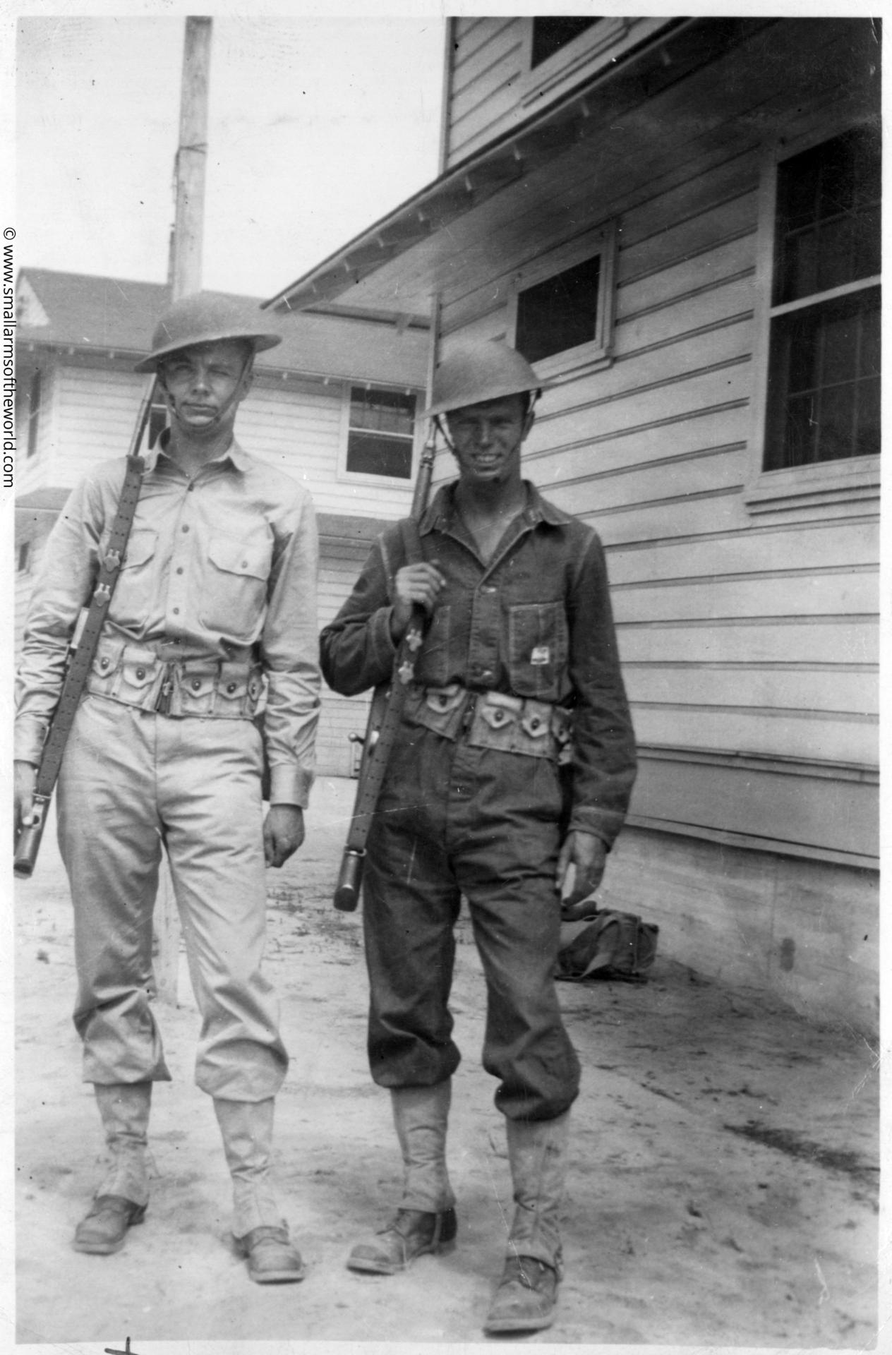 Two US soldiers with M1903 Springfield rifles next to a1930s style barracks.