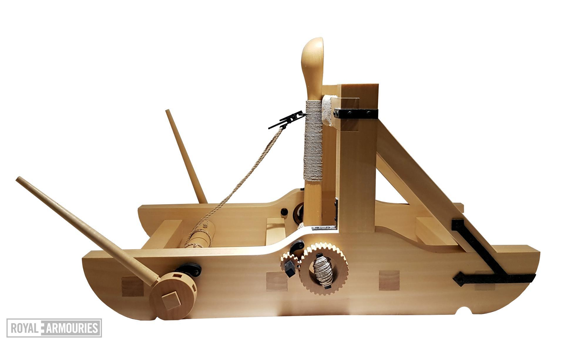 Wooden model of a torsion catapult or mangon. The throwing arm terminates in a carved wooden cup. The arm is thrust through a skein of twisted cords with the pressure being maintained via blackened metal ratchets at each side, and adjusted by a blackened metal lever. There are two removable wooden levers for turning the windlass in order to haul back the throwing arm. British, 1994 (M.92)