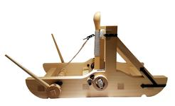 Thumbnail image of Wooden model of a torsion catapult or mangon. The throwing arm terminates in a carved wooden cup. The arm is thrust through a skein of twisted cords with the pressure being maintained via blackened metal ratchets at each side, and adjusted by a blackened metal lever. There are two removable wooden levers for turning the windlass in order to haul back the throwing arm. British, 1994 (M.92)