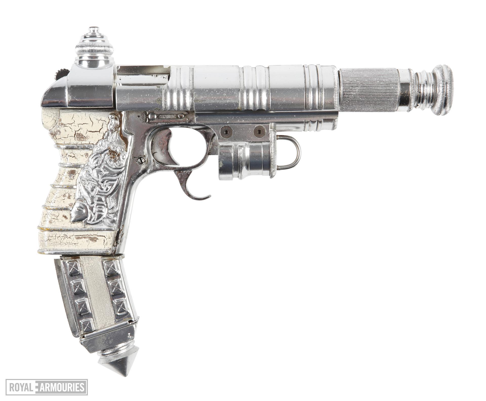 Prop pistol from the 2003 movie 'The League of Extraordinary Gentlemen'. Made from a Tokarev TT33 pistol dressed with painted plastic parts. Converted to fire movie blanks using an internal barrel restrictor. Used in the movie by Captain Nemo and some of his crew. Intended to suggest a Victorian weapon ahead of its time, following the 'Steampunk' retro-futuristic aesthetic of the movie and the graphic novel that it was based upon. European, about 1940 (XII.11938)