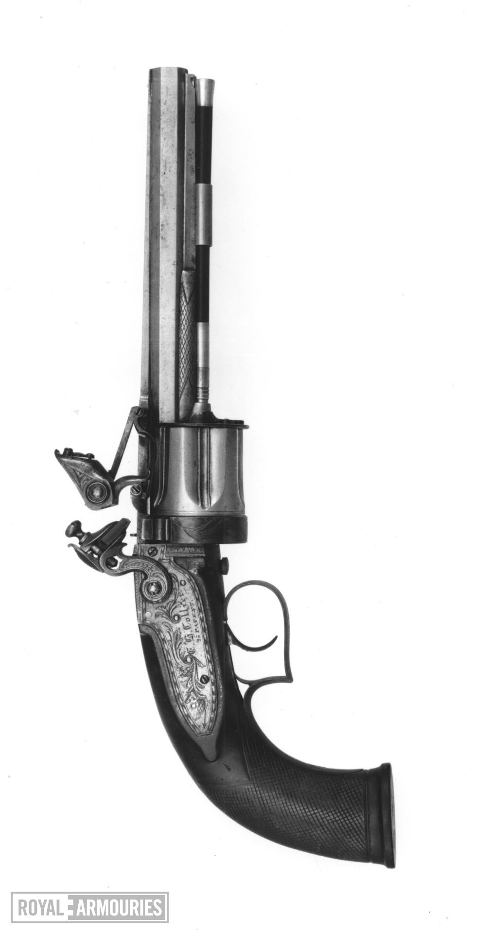 Flintlock six-shot revolver - Collier Patent By Collier. A revolving cylinder pistol that requires the cylinder to be manually turned. It has an octagonal barrel, with single pipe for a wooden cleaning rod. The cylinder is six-shot, and has a frizzen mounted to the right of the barrel, as would normally be found on a standard flintlock pistol. The rotation of the cylinder permits the touch-hole to line up with the frizzen. There is a sliding cover over the touch hole. The trigger guard is squared at the rear, and the butt is fully chequered. The lockplate, tang and top of the barrel are foliate engraved, with the Union Jack and Stand of Arms also incorporated.