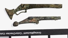 Thumbnail image of Top - Fish-tail butt toy musket of brass. English, about 1600 (XII.10701) Bottom - Matchlock toy pistol, brass, found during excavations near the White Tower, 1956. English, about1600 (XVIII.125)